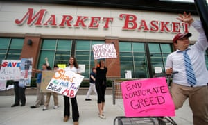 Market Basket employees Rees Gemmell, far right, and colleagues acknowledge passing supporters as they picket in front of the supermarket.
