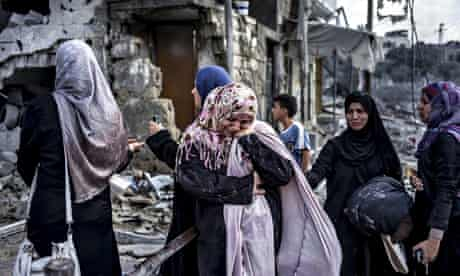 Palestinian women react to the destruction in Beit Hanuon, northern Gaza Strip, during the ceasefire