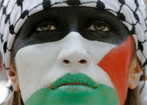 London, UK: A demonstrator with their face painted in the colours of the Palestinian flag protests outside the Israeli embassy