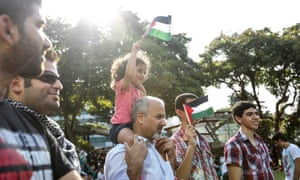 Singapore: A girl sits on her father's shoulders waving a Palestinian flag at a protest in Hong Lim Park