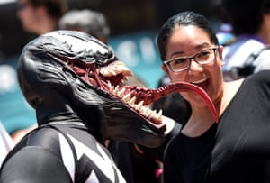 """Kaleb McDade, dressed as the Spiderman villian """"Venom,"""" poses for photos outside the San Diego Convention Center on the third day of the 45th."""