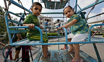 Palestinian children on a swing in Gaza City on the first day of Eid