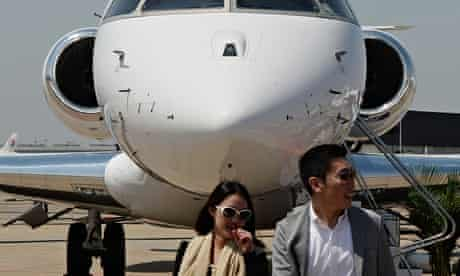 Chinese visitors to a business aviation exhibition walk in front of a private jet