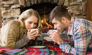 Romantic couple drinking tea in front of lit fireplace
