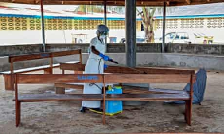 Nurse in Liberia disinfects waiting area for visitors
