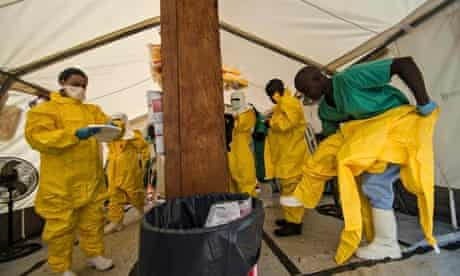 Medical staff put on their protective gear in Sierra Leone