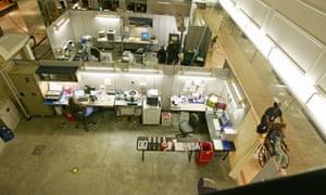A nurse's assistant wheels a patient past a makeshift laboratory hospital