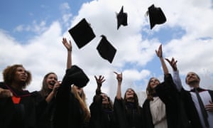 Students throw their hats in the air at their graduation ceremony