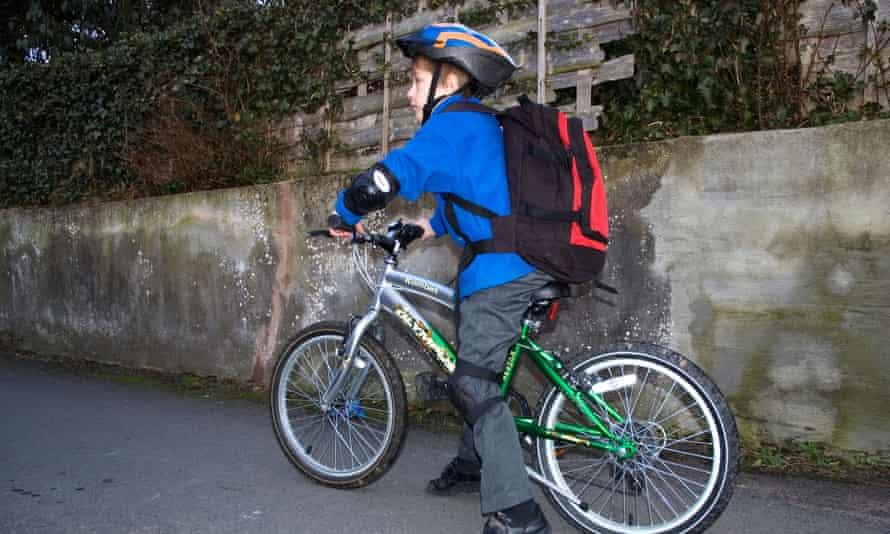 A boy cycles to school.