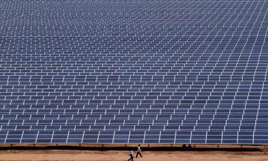 Indian workers walk past solar panels at the 200 megawatts Gujarat Solar Park at Charanka in Patan district, India, Saturday, April 14, 2012.