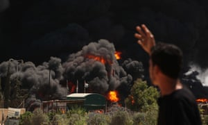 Palestinian men stand looking as flames engulf the fuel tanks of the only power plant supplying electricity to the Gaza Strip after it was hit by overnight Israeli shelling, in the south of Gaza City.