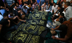 A Palestinian mourners gather around the bodies of fifteen members of the Abu zeid, Duheir and al-Hashash families, that were killed in an Israeli air strike on their home, during the funeral in Khan Yunis in the southern Gaza Strip on July 29, 2014.