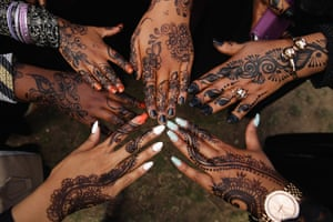 Girls show off their henna tattoos during an Eid celebration in London
