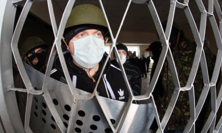 Masked pro-Russia fighters stand guard inside the regional police building in Gorlovka