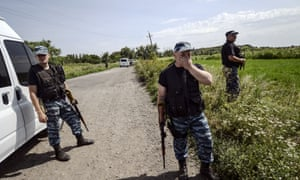 Pro-Russian militants stand guard as investigators  work at the crash site of the Malaysia Airlines Flight MH17