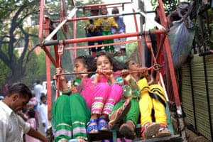 Children wear new clothes as they enjoy a ride on a hand-cranked ferris in Delhi