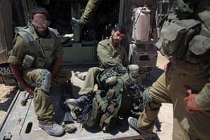 Israeli reserve soldiers prepare to enter the Gaza Strip near the Israel Gaza border, Tuesday, July 29, 2014.
