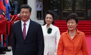Chinese President Xi Jinping, his wife Peng Liyuan and South Korean President Park Geun-Hye walk towards a guard of honour during a welcoming ceremony held at the presidential Blue House on 3 July, 2014 in Seoul.