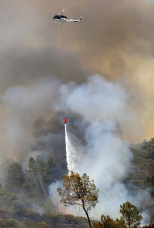 A helicopter drops water on Butts Fire