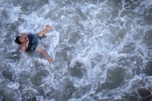 A woman gets knocked over in the surf on Coney Island in Brooklyn, New York