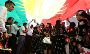 Iraqi Kurds hold a giant flag of their autonomous region in a demonstration calling for independence