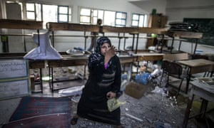 A desperate Palestinian woman throws debris in the air at the classroom where she is taking shelter with her family on July 30, 2014 following Israeli army shelling in the area. An Israeli shelling on the UN school being used as a shelter in the northern Gaza Strip killed 20 people today, medics said.