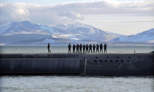 British Navy personnel stand atop the Trident nuclear submarine, HMS Victorious, on patrol off the west coast of Scotland in April 2013.