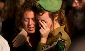 An Israeli woman and a soldier hug during the funeral of Sgt. Barkay Shor, who was killed in fighting in Gaza