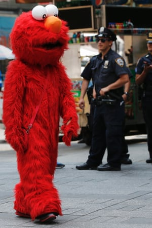 A person dressed as the Sesame Street character Elmo walks through Times Square in New York