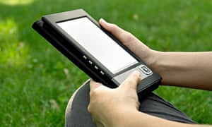 Young woman reads electronic book sitting on the grass. Shallow depth of field.