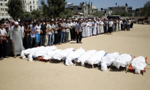 Palestinian mourners pray in front of the bodies of ten members of the al-Astal family, that were killed in an Israeli air strike on their homes, during their funeral in Khan Yunis in the southern Gaza Strip on July 30, 2014.