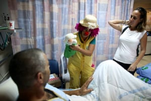 An Israeli woman dressed as a clown tries to cheer up an injured Israeli soldier who was wounded in fighting in the Gaza Strip, in the Soroka Hospital in Beersheba, Israel, 30 July 2014.