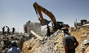 Palestinian rescue workers search for victims in a building destroyed by an Israeli air strike