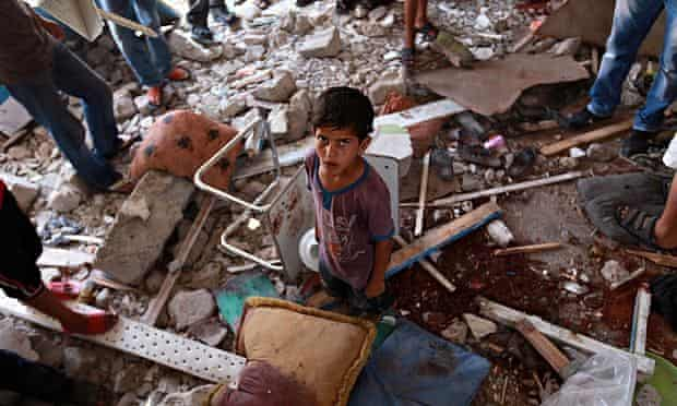 Palestinians inspect a damaged classroom of the UN school in Jabalia, northern Gaza, 30 July 2014.