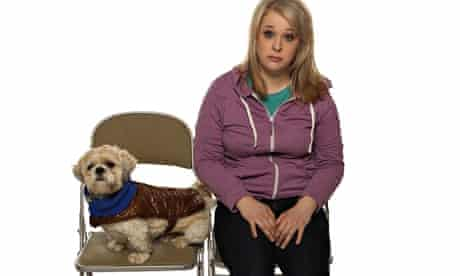 Hayley Ellis sits on a chair looking miserable, with a dog on a chair next to her