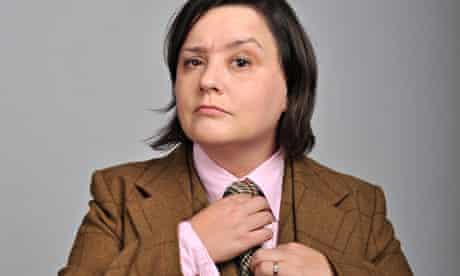 Susan Calman in brown three-piece suit adjusts her tie