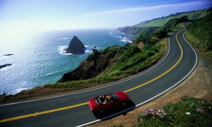 Person driving convertible on a coastal highway in California.
