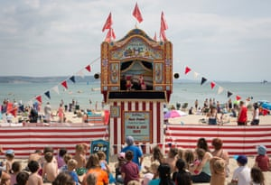 People watch a traditional Punch and Judy show on the beach in Weymouth.