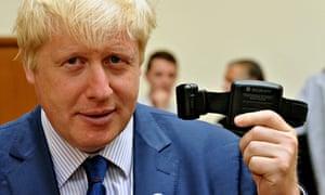 Boris Johnson holds a alcohol monitoring tag