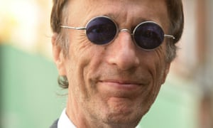 Robin Gibb, wearing round tinted classes, smiles at he camera