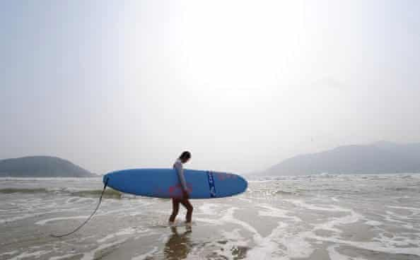 Surfing in the South China Sea at Houhai beach on Hainan island, China.