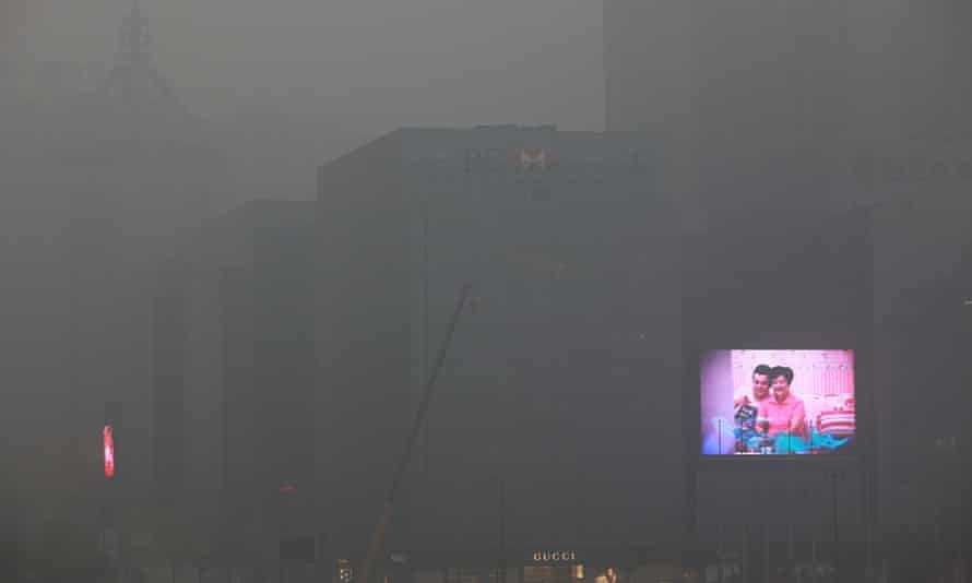 A big screen flashes commercials on the exterior of an office building in Xi'an in northwest China's Shaanxi province 15 December 2012 as  air quality index reaches 282 due to pollution.