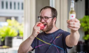 Bar owner Jozef Czarnocki bites an apple and holds a bottle of cider in defiance of Russia's ban