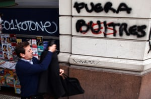 """A man walks by a graffiti that reads """"Get out vultures"""" in Buenos Aires, July 31, 2014."""