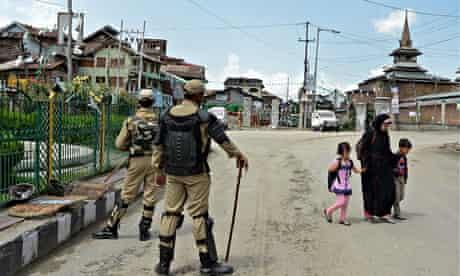 A Kashmiri family walks past Indian paramilitary troopers in Srinagar