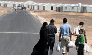 Syrian refugee family walks towards the new Syrian camp of Azraq