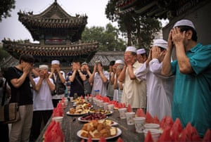 Chinese Muslims of the Hui ethnic minority pray over food before breaking fast