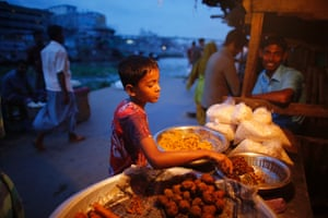 A boy sells food by the river Buriganga in the evening in Dhaka