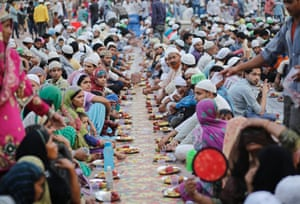 Indian Muslims sit before having their Iftar in the old quarters of Delhi