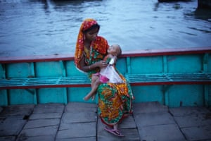 A woman eats with her child by the river Buriganga during the holy month of Ramadan in Dhaka, Bangladesh